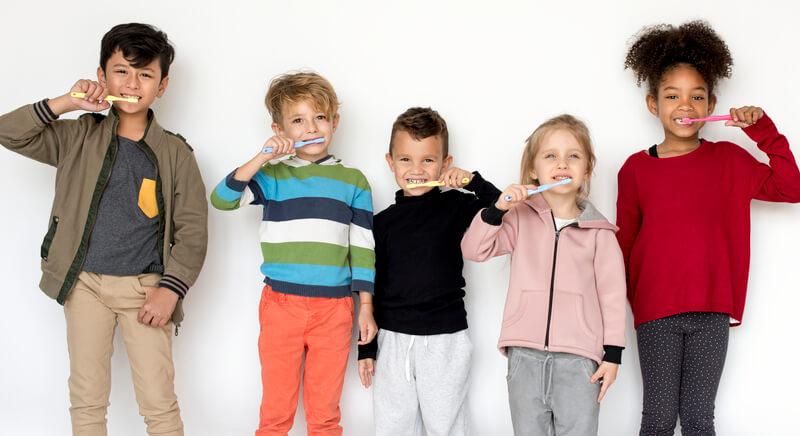 Kids standing in line brushing teeth.
